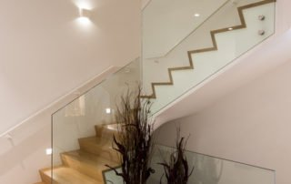 Glazen balustrade bij houten trappen