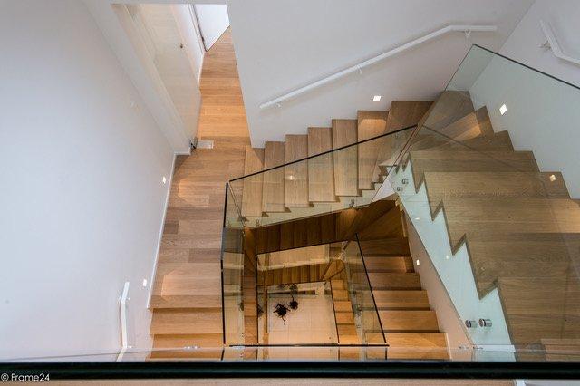 Glazen balustrade bij deze houten trap