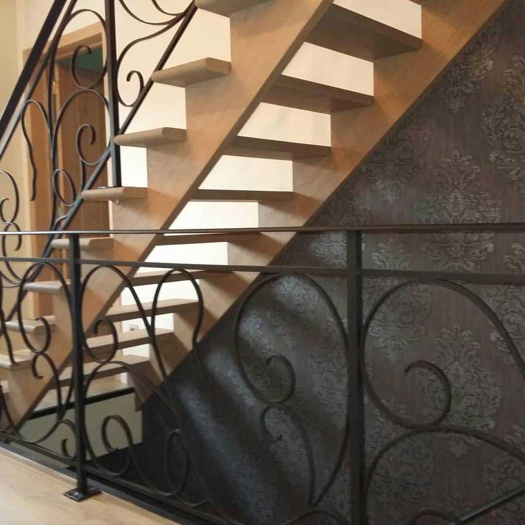 prachtige krullende ijzeren balustrade die doorloopt op de open trap