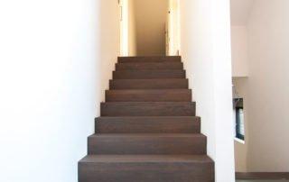 Bekleden van een betonnen trap met beuken panelen die nadien geolied werden. Trede nummer 1 is een bloktrede.