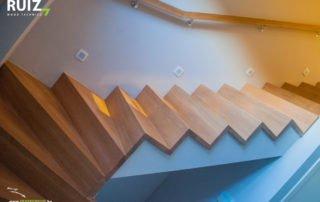 houten trap met led spotjes afgewerkt. Houten vierkanten muurgreep aan de muur.