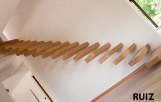 Open zwevende trap die vastzit door ijzerwerk in de muur