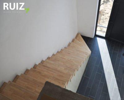 design trap met led verlichting aan de zijkant. Trap is bekleed op een betonnen ondertrap met rubberwood panelen.